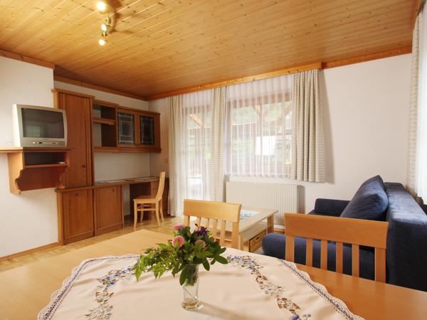 Auf dem Bild sieht man ein Wohnzimmer mit Couch und einem Eßtisch