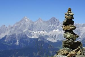 Man sieht einen gestapelten Haufen Steine vor der Bergkulisse des Dachstein - Massivs. Es ist ein strahlend schöner, wolkenloser Tag.