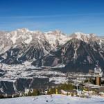 Panorama Planai - beliebter Hausberg zum Skifahren im Ennstal - ein wundeschöner Tag auf der Planai. Es sind Skifahrer zu sehen, im Hintergrund sieht man auf ein gewaltiges Bergmassiv.